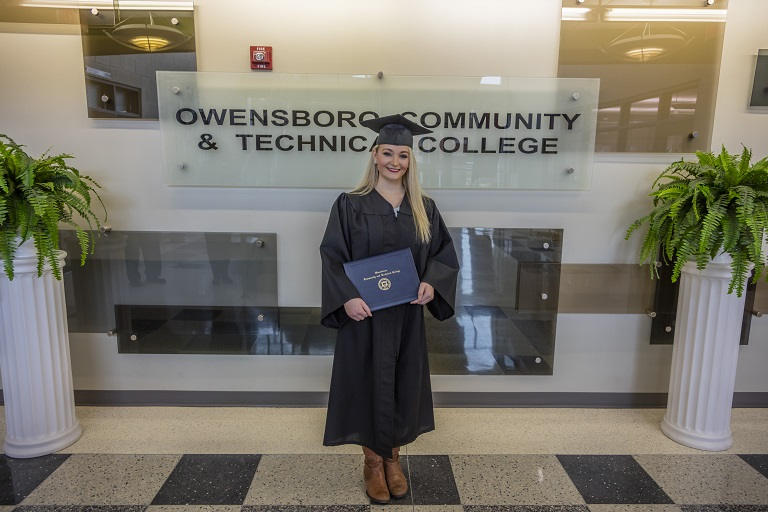 woman in cap and gown posing with her degree