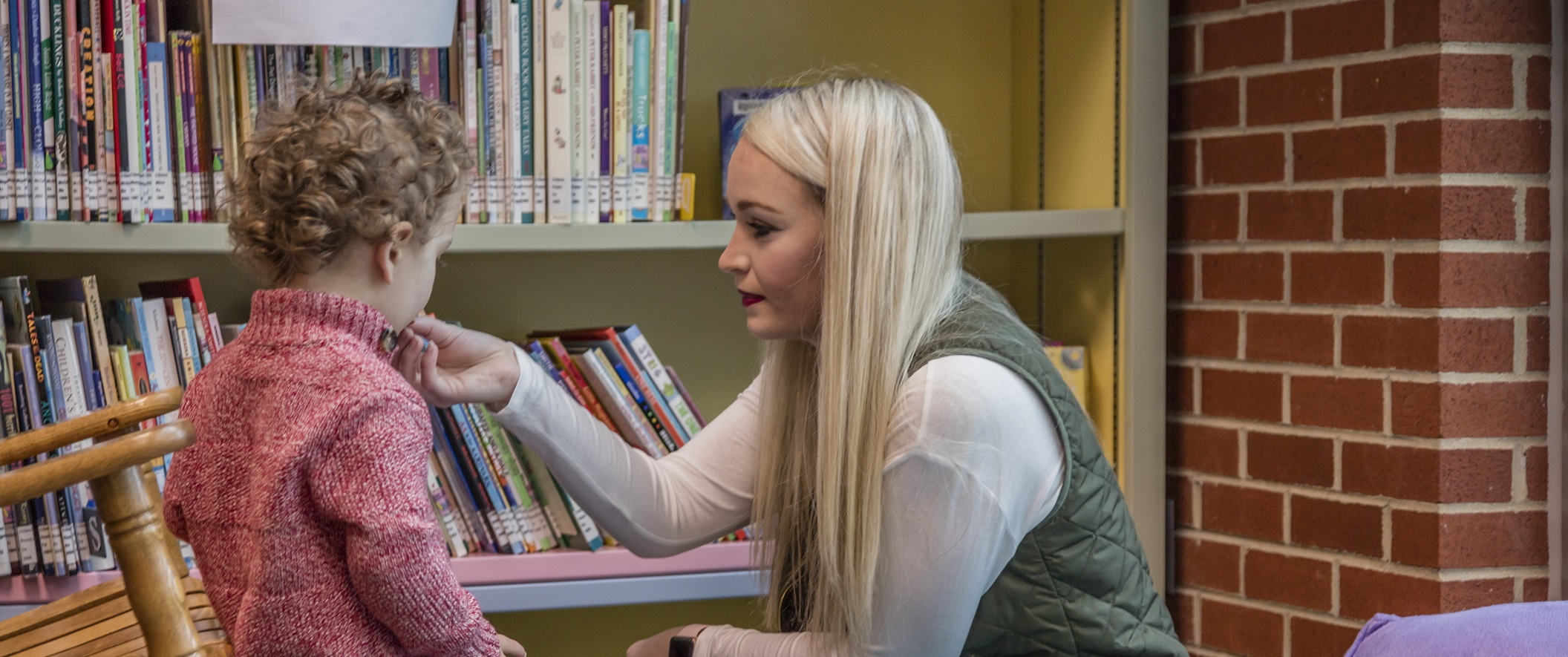 A mother interacting with her daughter in a library