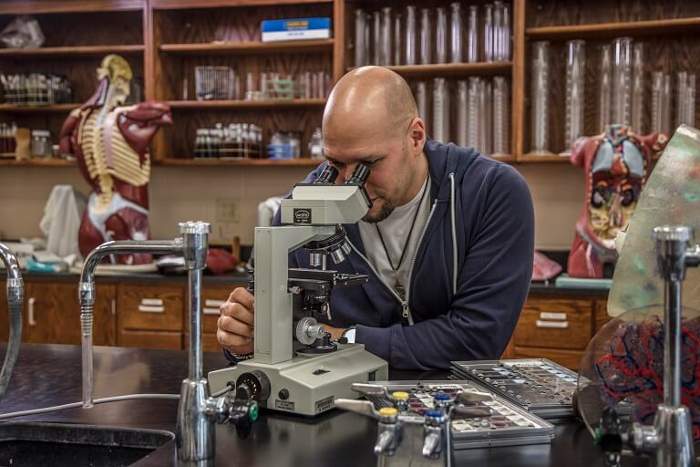African-American Student looking into microscope