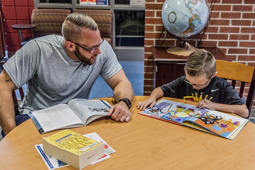 man and son reading in library